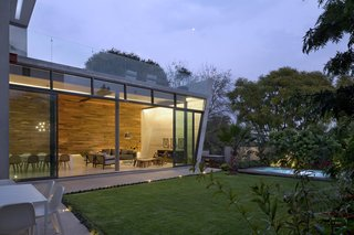 """Glass sliding doors allow the living and dining areas to open up to the garden, so that the family can easily entertain. """"The living room and dinning room are lined in wood to give them a warm feeling in contrast to the concrete floor and ceiling,"""" says Cesarman. The concrete wall features a chimney crafted of black granite for added visual interest."""