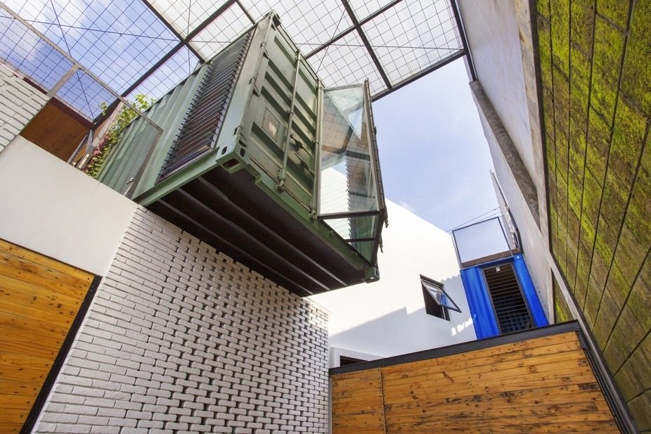 A rich pine exterior complements the brick, which was painted white as a means to minimize the use of cement.  In Indonesia, a Green-Roofed Container Home Stands Up to the Heat by Tiffany Jow
