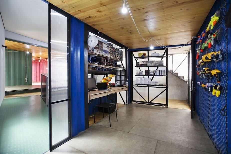 The hobby room features a custom desk and shelving system that Atelier Riri designed and manufactured themselves. A custom frame holds the family's tools and other objects on the eastern wall.  20 Ideas On What You Can Do With Old Shipping Containers from In Indonesia, a Green-Roofed Container Home Stands Up to the Heat