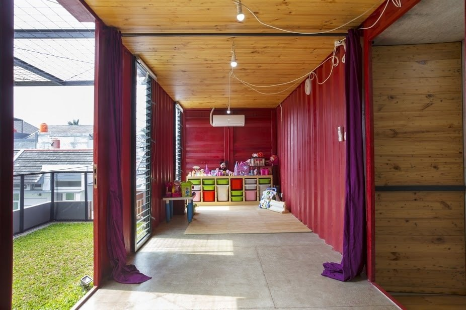 Kids Room, Playroom Room Type, Storage, Concrete Floor, Toddler Age, Neutral Gender, and Pre-Teen Age A cherry red game room gives way to a second green space on the roof, which can be used as an extension of the indoor space.  In Indonesia, a Green-Roofed Container Home Stands Up to the Heat by Tiffany Jow