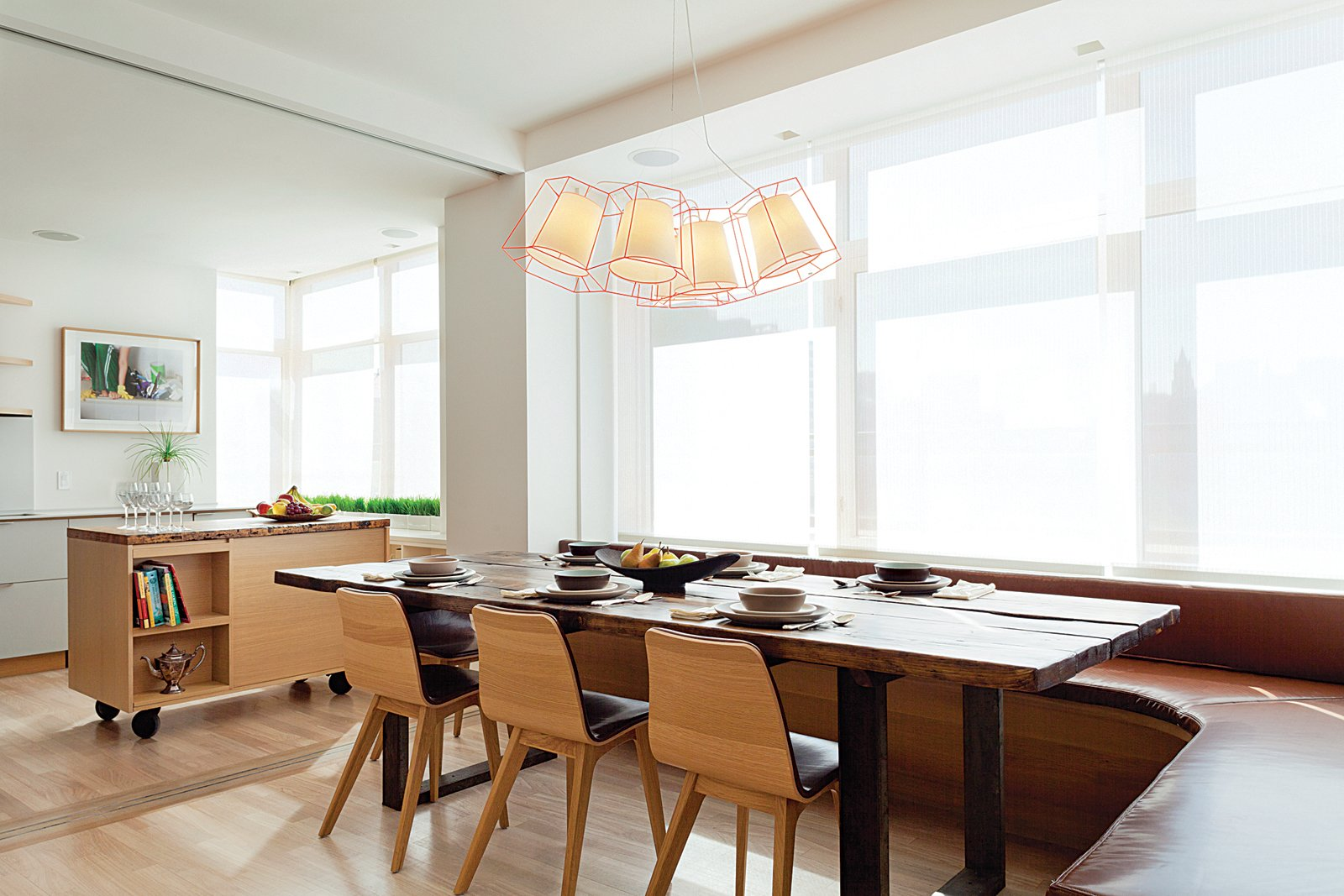 """Dining Room, Pendant Lighting, Chair, Table, and Light Hardwood Floor """"My directive was to create something very comfortable, calm, textural, and modern,"""" explains Reddy, who used a palette of reclaimed oak, bleached wood floors, blonde millwork, and white plaster. """"It's a space where you want to linger,"""" she says. An ExoFly pendant by Laurent Massaloux hangs above a custom WRK dining table surrounded by Morph side chairs by Zeitraum and a banquette covered in Glant's Liquid Leather.  Lovely NYC Abodes That Will Give You Apartment Envy by Allie Weiss from Light Fixtures We Love"""