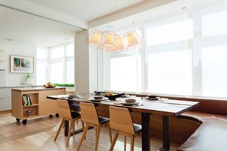 """""""My directive was to create something very comfortable, calm, textural, and modern,"""" explains Reddy, who used a palette of reclaimed oak, bleached wood floors, blonde millwork, and white plaster. """"It's a space where you want to linger,"""" she says. An ExoFly pendant by Laurent Massaloux hangs above a custom WRK dining table surrounded by Morph side chairs by Zeitraum and a banquette covered in Glant's Liquid Leather."""