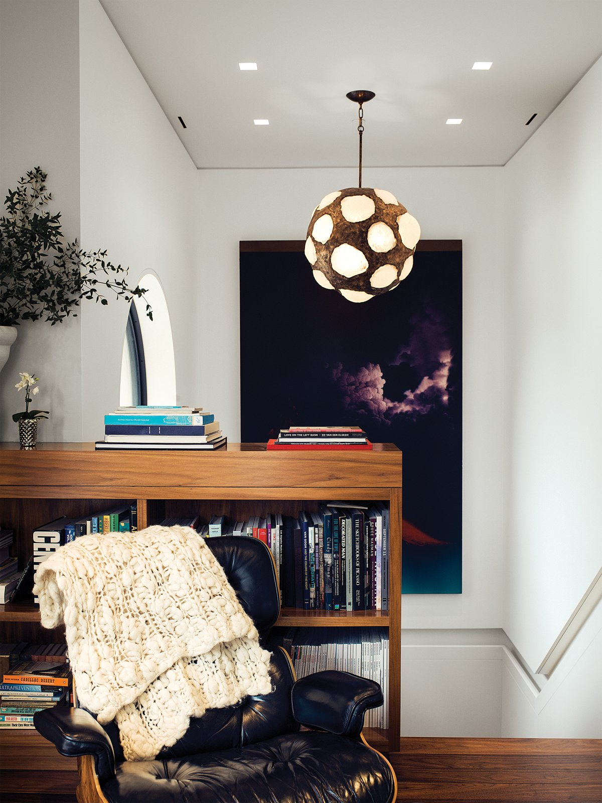At the top of the stairwell, a sitting area is outfitted with a vintage Eames lounge, a large Jack Goldstein painting, and a 1970s light fixture found by Marcovitz in Paris. Photo by João Canziani.  Loft