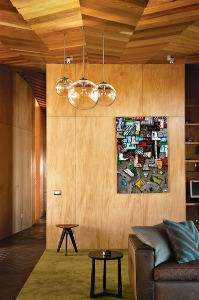 Michael O'Sullivan's blown-glass pendant lights make another appearance in the living area, where a kauri-plywood wall showcases a piece by artist Martin Poppelwell. Photo by Emily Andrews.