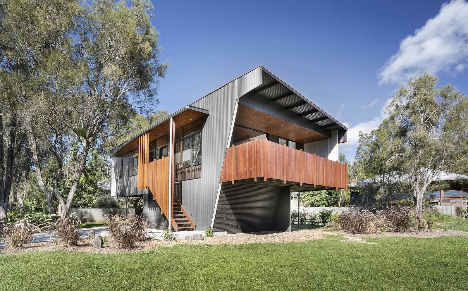 "Outdoor, Back Yard, and Grass The architects' inventive use of resources helped keep costs down. ""We gave the facade's ribbed metal cladding, commonly used in neighboring beach shacks, a metallic finish that provided a cost-effective solution and an upscale appearance,"" Rathmayr says.  Northern Rivers Beach House by Tiffany Jow"