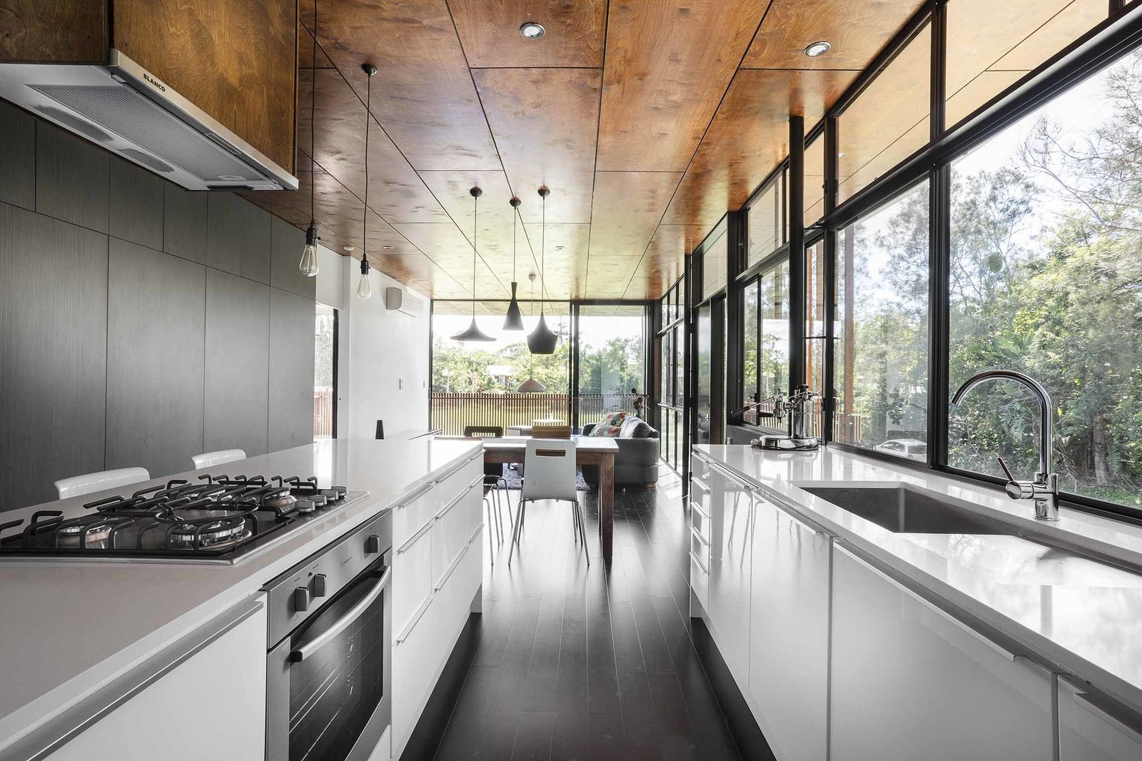 Kitchen, White Cabinet, Pendant Lighting, Range, and Undermount Sink In the kitchen, a Blanco exhaust fan is surrounded by a stove, oven, and dishwasher by Westinghouse. A series of pendants by She Lights are equipped with LED fittings.  Northern Rivers Beach House by Tiffany Jow