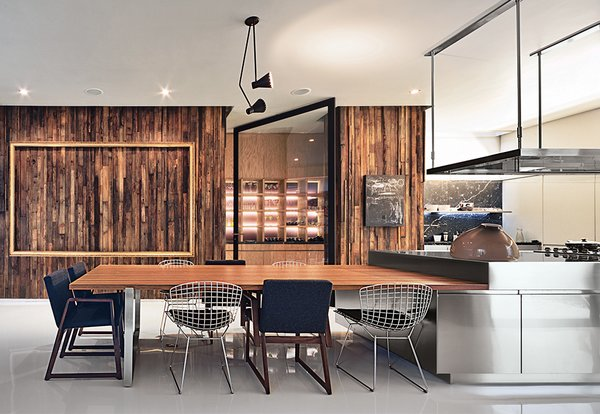 A vintage Lightolier pendant and sleek Arclinea cabinets by Antonio Citterio stand out against a wall paneled in reclaimed pine in the kitchen. Seating is a mix of Bertoia wire chairs and armchairs by the Mexican designer Hector Esrawe.