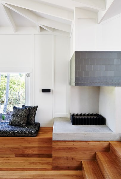 In the living area, an EcoSmart Fire ethanol-fueled fireplace is lined in charcoal tile by Winckelmans; the bench cushion is upholstered in Gillespie Onyx from Warwick Fabrics.