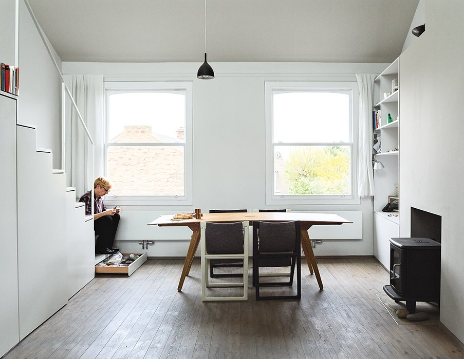 Dining, Chair, Pendant, Wood Burning, Shelves, Medium Hardwood, and Table The stairs lead to a sleeping loft outfitted with a mechanical skylight.  Best Dining Shelves Table Pendant Chair Medium Hardwood Photos from This Is How You Can Live Large in a Small Space