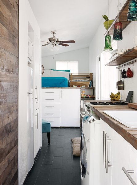 Porcelain floor tile from Daltile is a durable, easy-to-clean substitute for wood. The family does laundry in an efficient Summit SPWD1800 washer-dryer combination unit. Miller saved money in the kitchen by using a reclaimed sink and faucet and drawer pulls from Ikea.