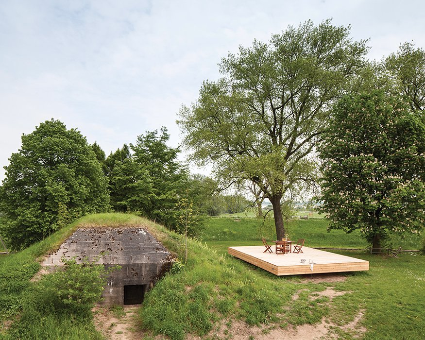 Exterior, House Building Type, Cabin Building Type, and Concrete Siding Material Architect Bruno Despierre built a deck for outdoor activities from pine wood.  Best Photos from Dutch Military Bunker Becomes Tiny Vacation Home