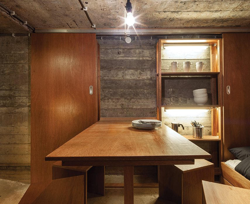 Dining Room, Bench, and Concrete Floor Custom-designed furniture outfits the interior of a bunker-turned-vacation retreat in the Netherlands.  Best Photos from Dutch Military Bunker Becomes Tiny Vacation Home