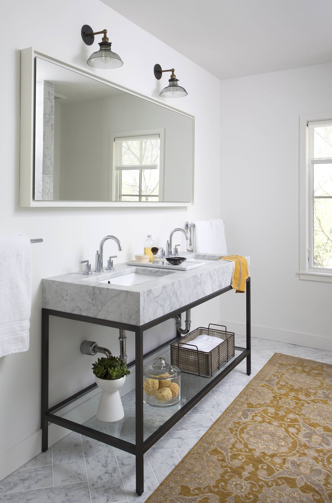 "Bath Room, Marble Counter, Marble Floor, Wall Lighting, Undermount Sink, and Rug Floor White walls, a luxurious marble double-sink, and an area rug give this bathroom an inviting atmosphere. ""The natural light, open spaces, and light color palette make it a great place to wake up in the morning,"" Flournoy says of his home. The sink is from Restoration Hardware and the rug is from West Elm.  Photo 7 of 8 in Modern Take on a Texas Farmhouse"