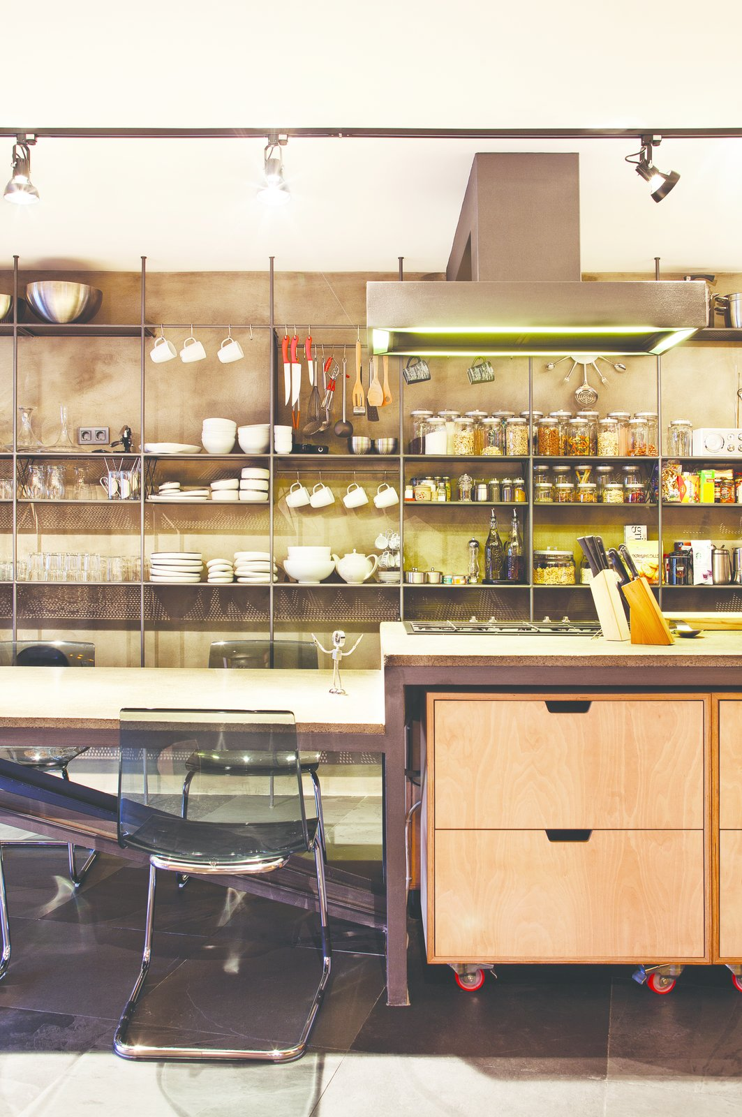 "Kitchen The kitchen worktop is framed in iron, and functional wheeled storage fits perfectly underneath. The full-wall shelving system offers ample storage for dishware and cooking accessories.  Search ""5 gravity defying cantilevers"" from A Single-Room Loft with Impressive Wall-to-Wall Storage"