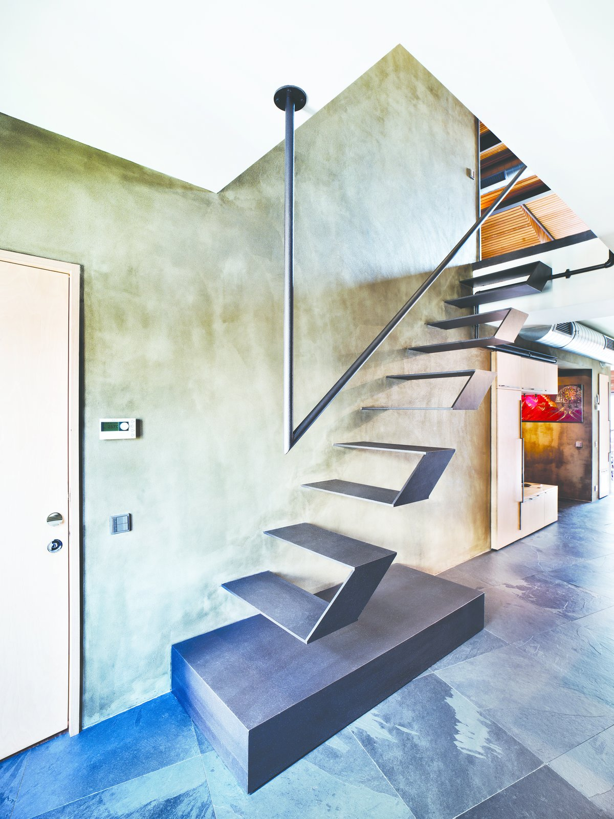 Futuristic floating stairs lead to the loft's mezzanine. Throughout the lower level, natural stone was chosen for the flooring, laid at an irregular angle to add visual interest. Tagged: Staircase, Metal Railing, and Metal Tread.  Loft from A Single-Room Loft with Impressive Wall-to-Wall Storage