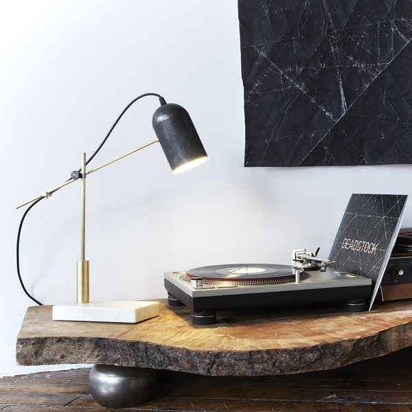 The Deadstock Catherine Table Lamp from Castor is a stunning example of the possibilities of mixing materials. Centered around a cylindrical shade salvaged from a defunct lighting factory, the Catherine Lamp is supported by a precisely machined brass stem and cantilever, which is supported by a Carrara marble base that was salvaged from the First Canadian Place in Toronto. The structure of the lamp enables it to be adjusted, making it easy to redirect light as needed.