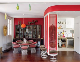 A far cry from minimalism, the renovated 900-square-foot Paris flat belonging to Nicolas Roche, a scion of the French furniture company Roche Bobois, is decked out with vivid hues and vintage furniture. A 1960s orange lamp by Luxus is suspended over the Warren Platner dining table and chairs. The 1950s rosewood glass cabinet is from Soriano. Pod Lens pendants by Ross Lovegrove for Luceplan hang from the ceiling.