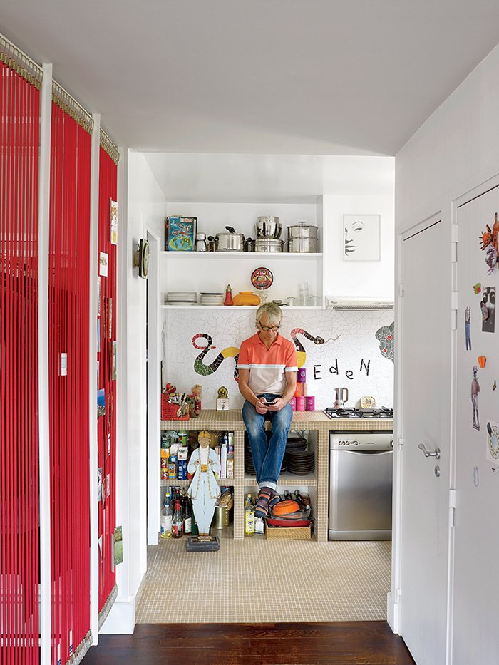 "Kitchen, Dishwasher, Mosaic Tile Backsplashe, and Tile Counter An architect by profession, Roche removed as many partitions as he could when recasting the apartment's interior, preferring transparency. He custom-made the red room divider from bungee cords.  Search ""paris landmarks architectural print unframed"" from This Petite Paris Apartment is a Vintage Furniture–Filled Delight"