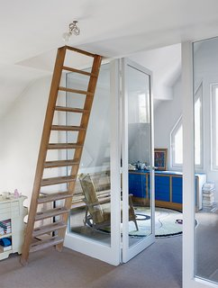 A ladder leads to a guest room in the attic. The striking-blue bedroom dresser was part of a modular storage system installed by the previous owner.