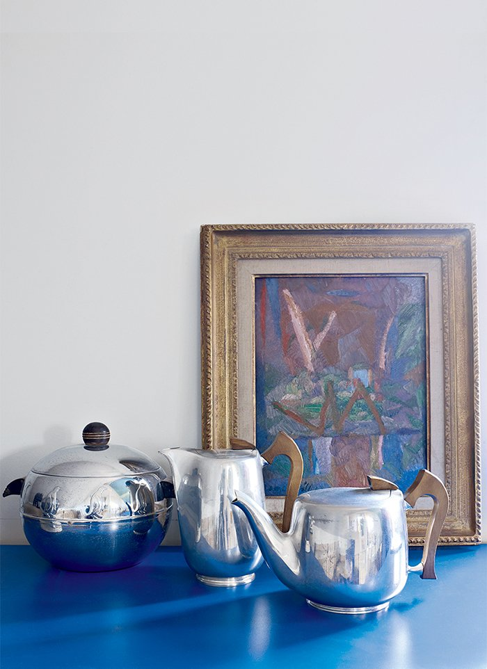 Living Room Antique tea and chocolate pots are juxtaposed with a 1930s painting by Jacques Villon, Marcel Duchamp's brother.  Photo 6 of 9 in This Petite Paris Apartment is a Vintage Furniture–Filled Delight