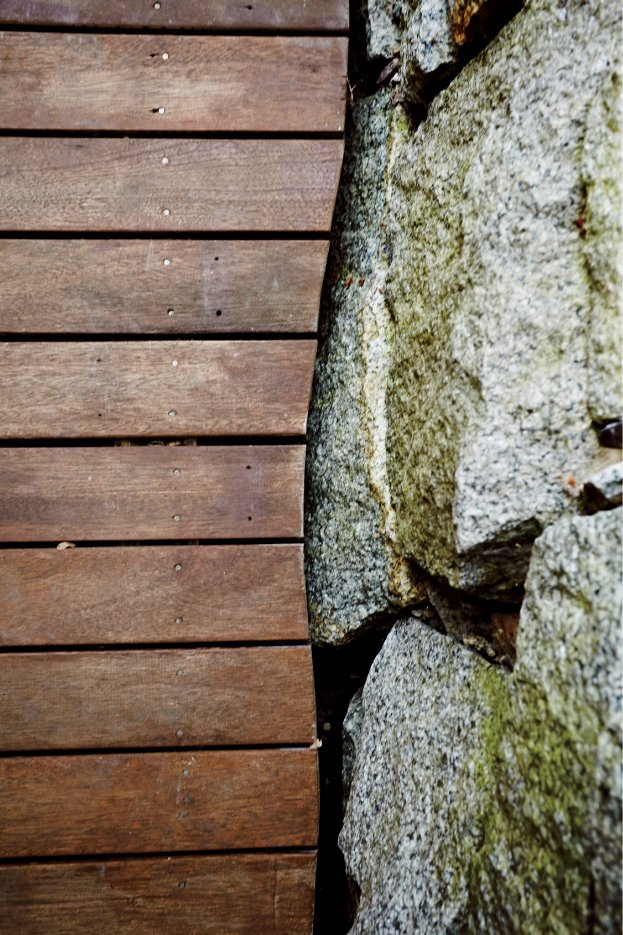 Outdoor Design details include mahogany and granite where the deck meets a stone retaining wall.  Photo 7 of 8 in A Family Builds a Tiny Backyard Studio on an Even Tinier Budget