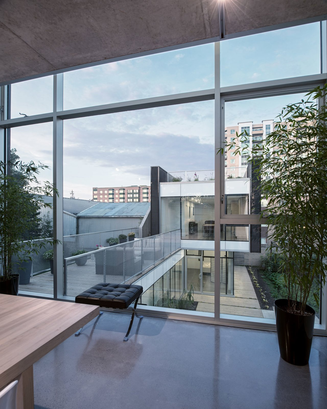 Windows and Picture Window Type The main living area is connected to the back unit by a modern bridge. Polished concrete is used for both floors and ceilings, and a Mies van der Rohe Barcelona Stool accents the space.  Best Photos