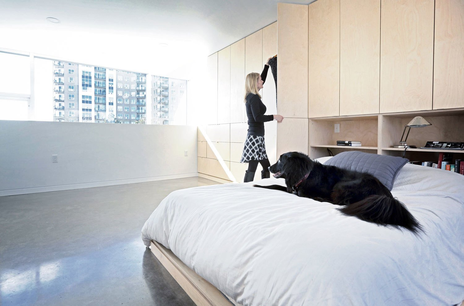 Bedroom, Bed, Storage, Shelves, Concrete, Recessed, and Table Concrete was chosen for both structural and finish material throughout much of the home, for its aesthetic, functional, and budgetary appeal. The polished concrete floors in the bedroom complement the birch bed and cabinetry. The home provides living space for the couple, two kids, one dog, and two cats.  Best Bedroom Table Shelves Recessed Photos from The Architect Next Door
