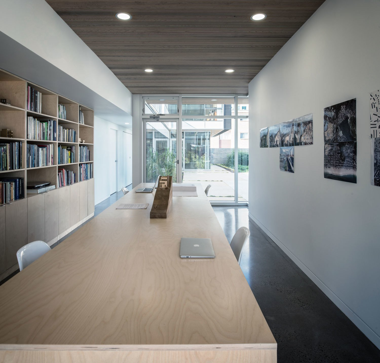 Office, Study Room Type, Shelves, Desk, Chair, and Bookcase Positioned on the ground floor, the office enjoys spacial privacy, while still having intimate interaction with the living area above and common courtyard.  Photo 9 of 9 in The Architect Next Door