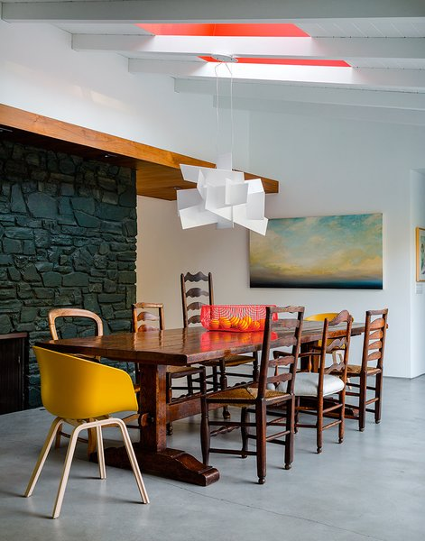 "Walnut panels and touches of bright red warm up the minimalist space, which the owners wanted to be ""clean, eclectic, and modern."" The pendant is Big Bang by Foscarini."
