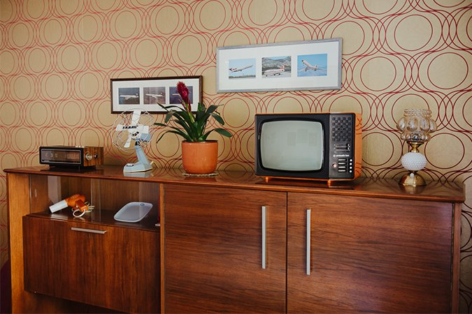 """The credenza is probably my favorite piece of furniture, and in the Yugodom I set up one in each room,"" Milakovic says. The piece in the 1970s-themed bedroom features an array of period products that the former owner bought in Trieste, Italy, a favorite destination for buying ""Western"" goods during the socialist era. All of the objects except the fan are marked Made in Yugoslavia.  Photo 2 of 5 in This Vacation Rental is a Living Museum of Midcentury Eastern European Design"