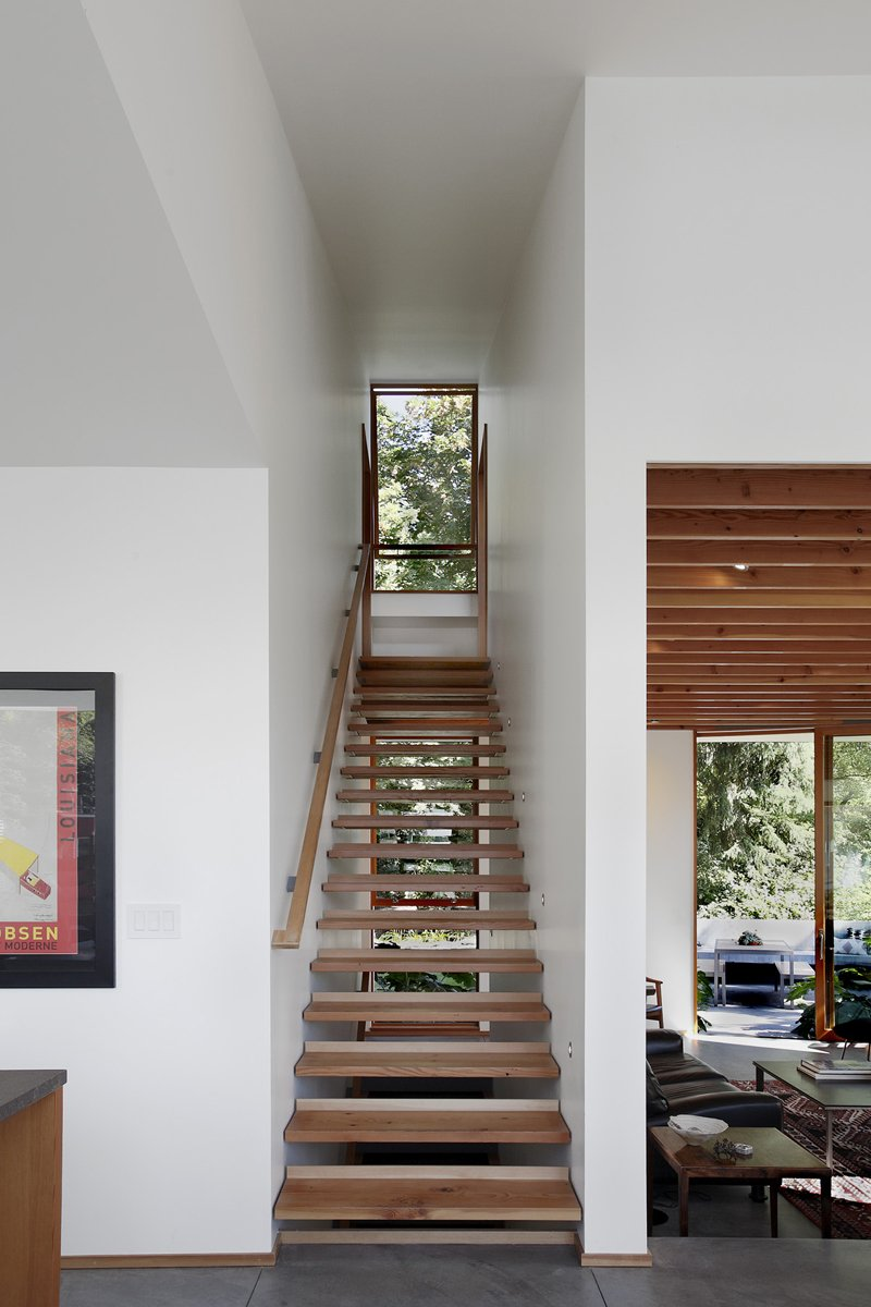 Staircase, Wood Tread, and Wood Railing The architects divided the home into separate floors for sleeping, living, and working. Since the house is situated on a hill that slopes 20 feet from top to bottom, there are plenty of stairs. Those pictured above were crafted using wood salvaged from a 100-year-old bungalow that previously stood on the site.  Photo 2 of 11 in Seattle Home Carefully Blocks Out Neighbors, While Celebrating Natural Surroundings