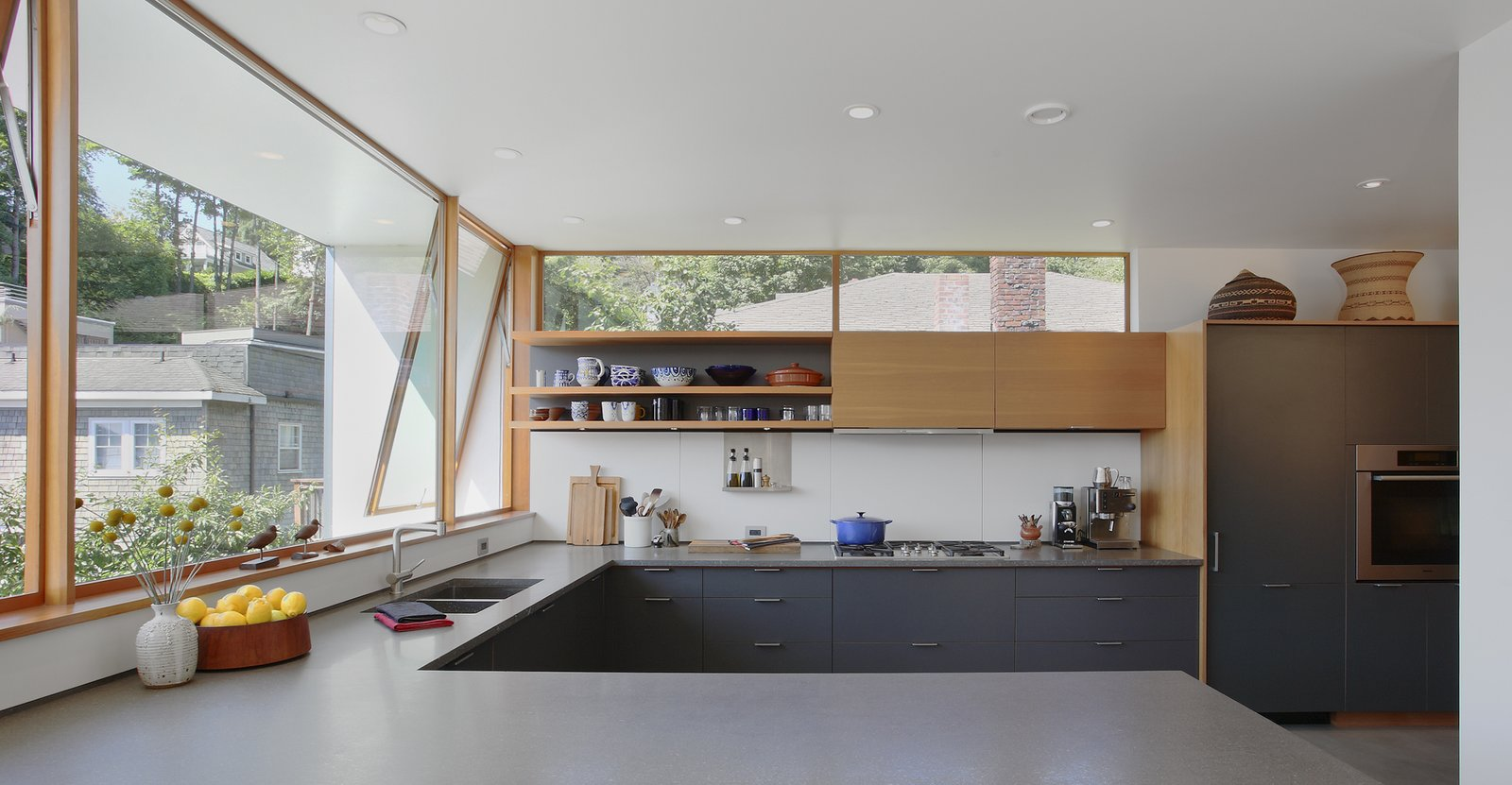 In the kitchen, a high western window carries the eye past neighboring rooftops to the lush hillside beyond. A wall also extends out to block sight of a neighboring deck. The architects paired custom shelving with slate-gray cabinets by Henrybuilt, cool Basaltina countertops, and white Corian backsplash. The faucet is by Cifial. Tagged: Kitchen.  Photo 3 of 11 in Seattle Home Carefully Blocks Out Neighbors, While Celebrating Natural Surroundings