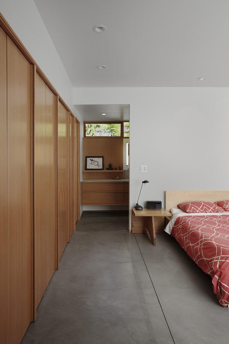 Bedroom, Night Stands, and Bed Located on the house's lower level, the bedroom is bright but soothing. The bed is flanked by custom side tables and covered with a red West Elm duvet.  Photo 6 of 11 in Seattle Home Carefully Blocks Out Neighbors, While Celebrating Natural Surroundings