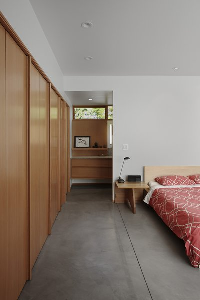 Located on the house's lower level, the bedroom is bright but soothing. The bed is flanked by custom side tables and covered with a red West Elm duvet.
