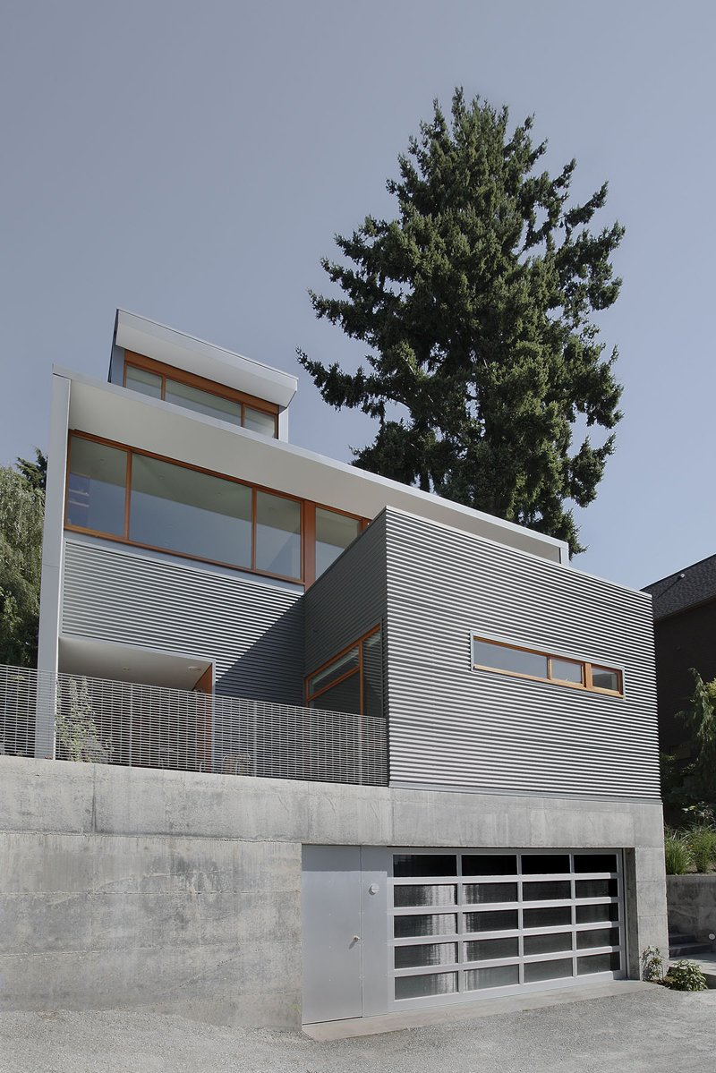 """Exterior and House Building Type A private terrace overlooks an alleyway on the main floor's southeastern end. """"[The home's] outdoor spaces are all to varying degrees extensions of interior space,"""" Schaer says.  Search """"staircasetread--metal"""" from Seattle Home Carefully Blocks Out Neighbors, While Celebrating Natural Surroundings"""