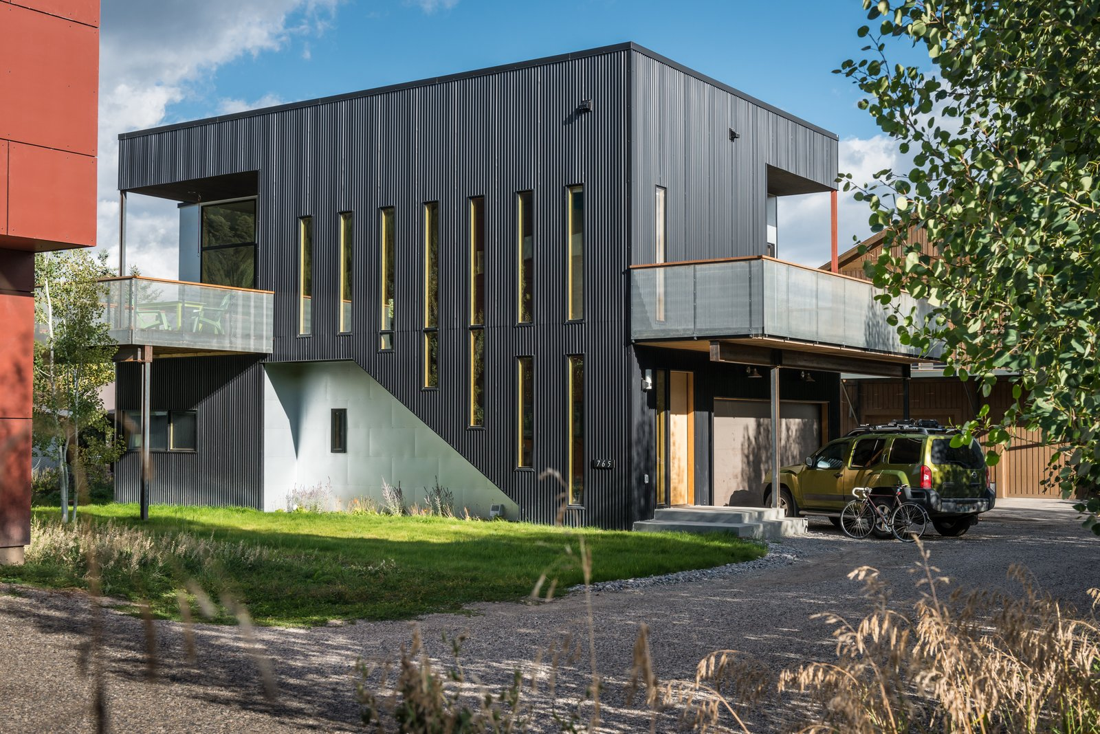 "Exterior, House Building Type, Metal Siding Material, and Flat RoofLine Galvanized sheet metal is used in places where the architects manipulated the home's skin by pushing it out or carving it away. The rest of the residence is wrapped in black corrugated sheet metal. ""We looked for exterior materials that were made with recycled content and available in large amounts, so as to reduce the number of hours painting the stuff,"" Logan says.  Photo 2 of 4 in House of the Week: Budget-Friendly Box Home"