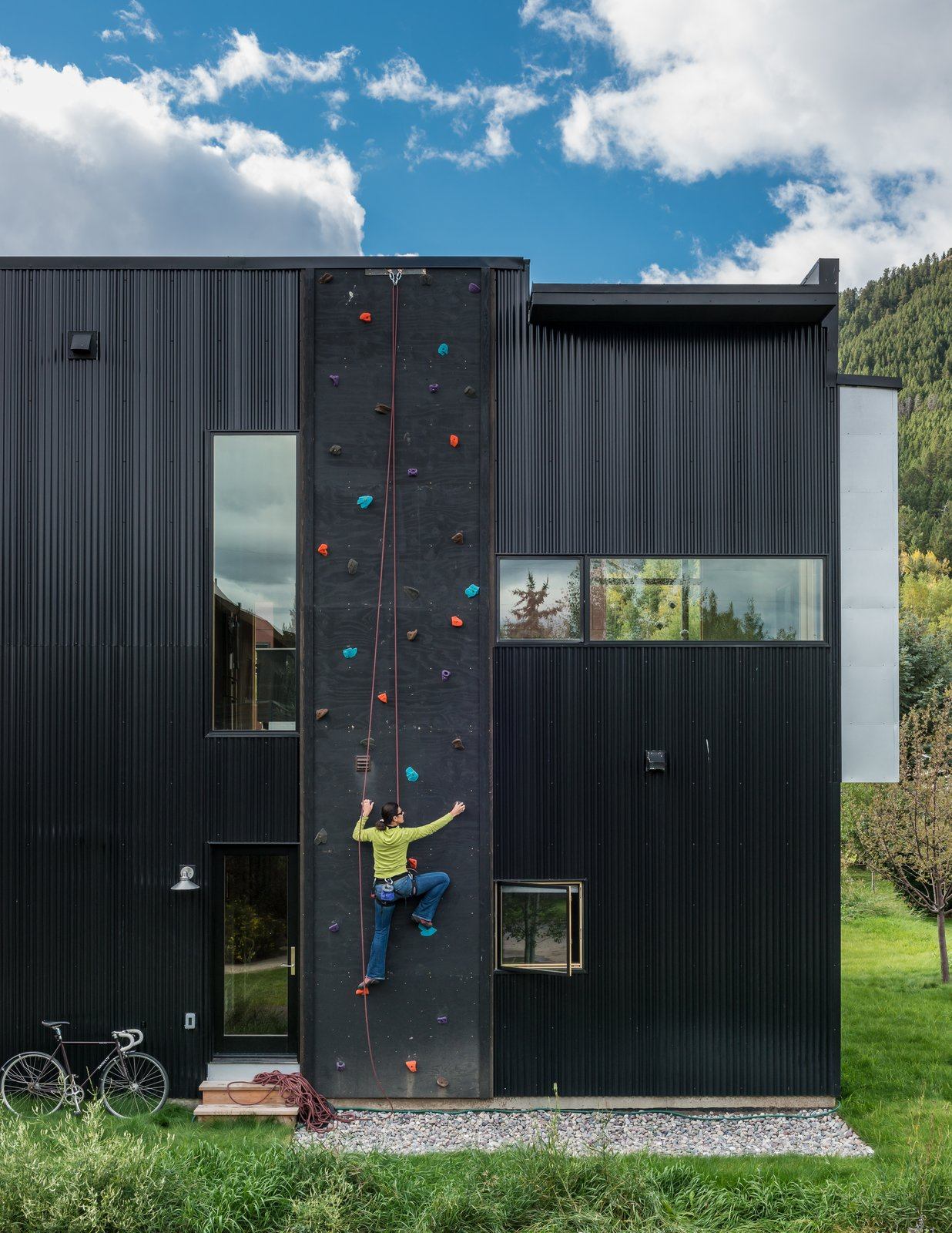 Exterior, House Building Type, Metal Siding Material, and Flat RoofLine Dotted with colorful footholds, a climbing wall covers one side of the home, allowing roof access.  Photos from House of the Week: Budget-Friendly Box Home