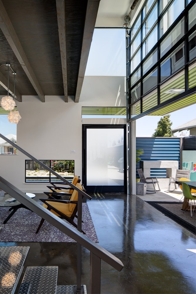 """The owner wanted an interior scheme that felt loft-like, so Rice and his team carved out the double-height space from the second floor to create the entryway aviary. The garage door feature adds urban grit to the space. """"We made it seem less like an actual garage door and more like a panel that just slides straight up,"""" Rice says.  Photo 4 of 10 in A Dull Stucco Home Becomes a Modern California Oasis"""