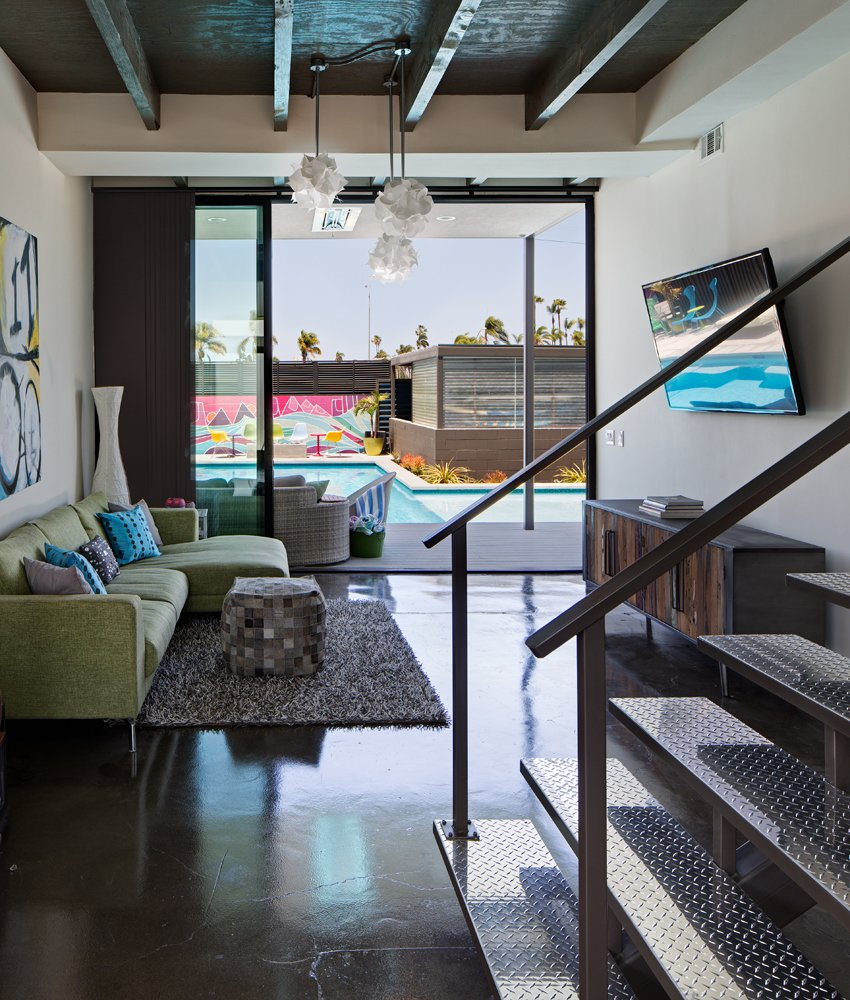 Loft-like features are used throughout the first floor interior space, including raw polished concrete floors, exposed beams (one of the few elements of the existing home that were preserved), and diamond-plate steel cladding on the floating staircase.  Photo 7 of 10 in A Dull Stucco Home Becomes a Modern California Oasis