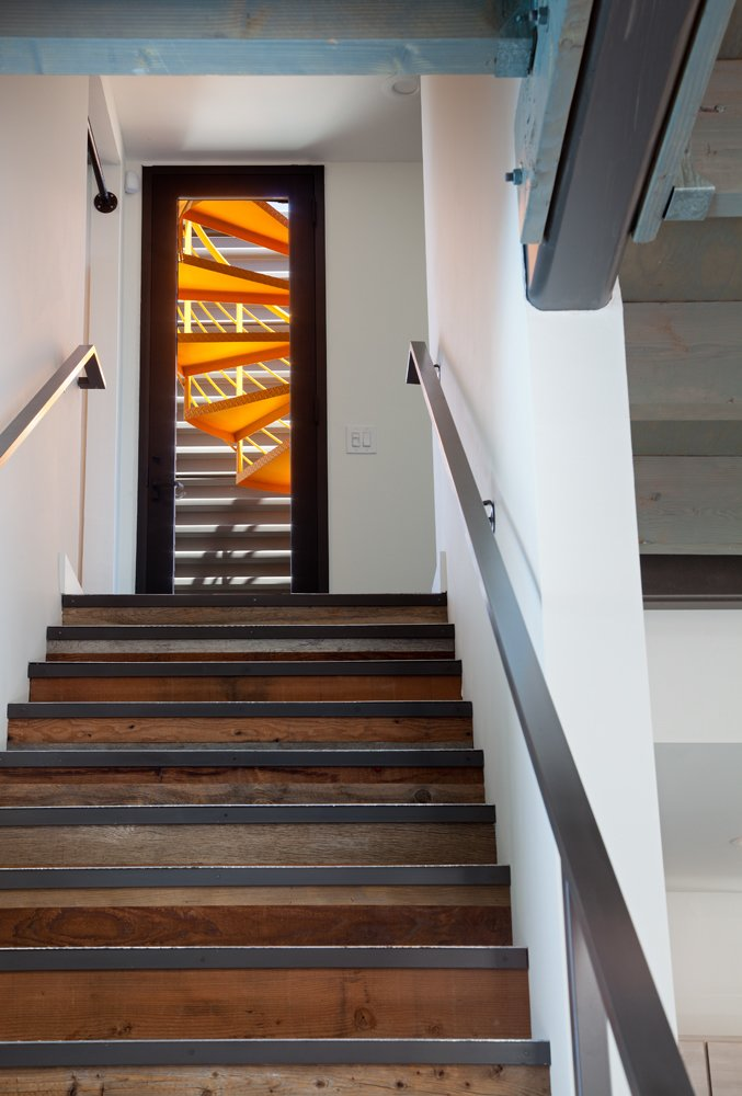 The staircase leads from the living room to an exterior balcony, where a second spiral staircase leading to the rooftop balcony was painted bright tangerine orange. The roof deck spans the entire footprint of the home.  Photo 9 of 10 in A Dull Stucco Home Becomes a Modern California Oasis
