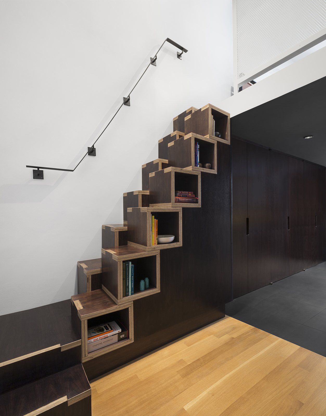 """Confronted with limited space to build the staircase needed to access the living area and bedroom on the second level, General Assembly designed a custom solution. """"These stairs are not an ideal design for everyone and shouldn't be used as primary stairs—we like to think of them more as millwork with a little bonus to it, than an actual staircase,"""" Zames says. """"The cube construction of the stairs actually came from a budget standpoint. We were very tight on budget and wanted to maximize the material as much as possible.""""  190+ Best Modern Staircase Ideas from Smart Staircases that Double as Storage"""