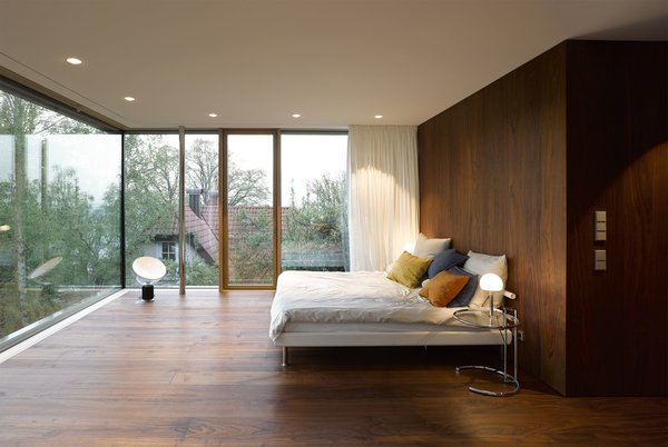 Light streams into the bedroom through walls of floor-to-ceiling glass. The windows are triple-glazed, creating a tight, eco-friendly seal. Tagged: Bedroom, Night Stands, Table Lighting, Floor Lighting, Bed, Dark Hardwood Floor, Lamps, and Recessed Lighting.  Renovations from An Uninspired Home in Germany Gets a Bright, Eco-Friendly Update