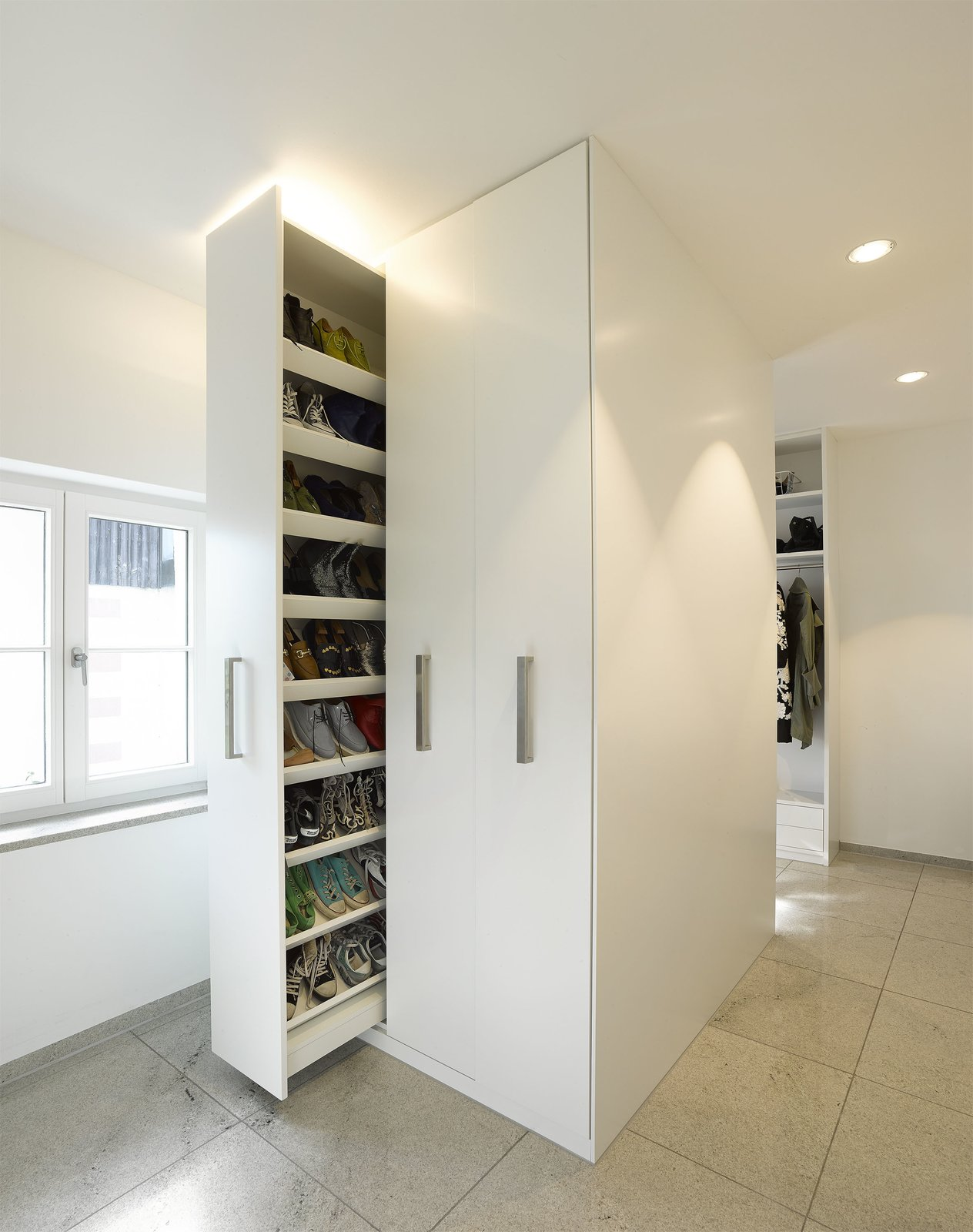 Though the home is expansive, the team made certain to waste as little space as possible. Clever moments of storage, like this sliding shoe closet, abound.  Renovations from An Uninspired Home in Germany Gets a Bright, Eco-Friendly Update