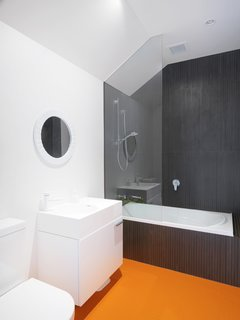 Low-maintenance, sustainable materials were favored throughout the house. Striking orange Pirelli studded rubber floors were chosen for the main bathroom. Clean white fixtures and black shower cladding complete the graphic space.