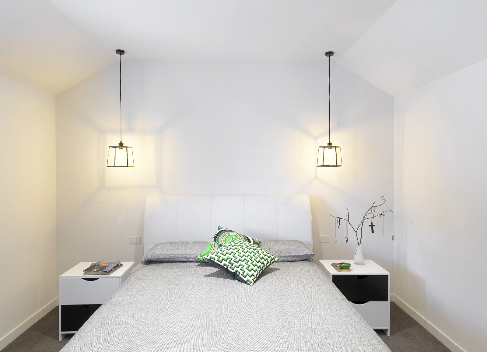 The renovated master bedroom preserves the slope of the original vaulted ceiling. A tufted headboard and suspended Q-BEE steel pendant lights accent the simple and elegant space.  Bedrooms by Dwell from 1850s Prefab Cottage from Boston Finds New Life in Australia