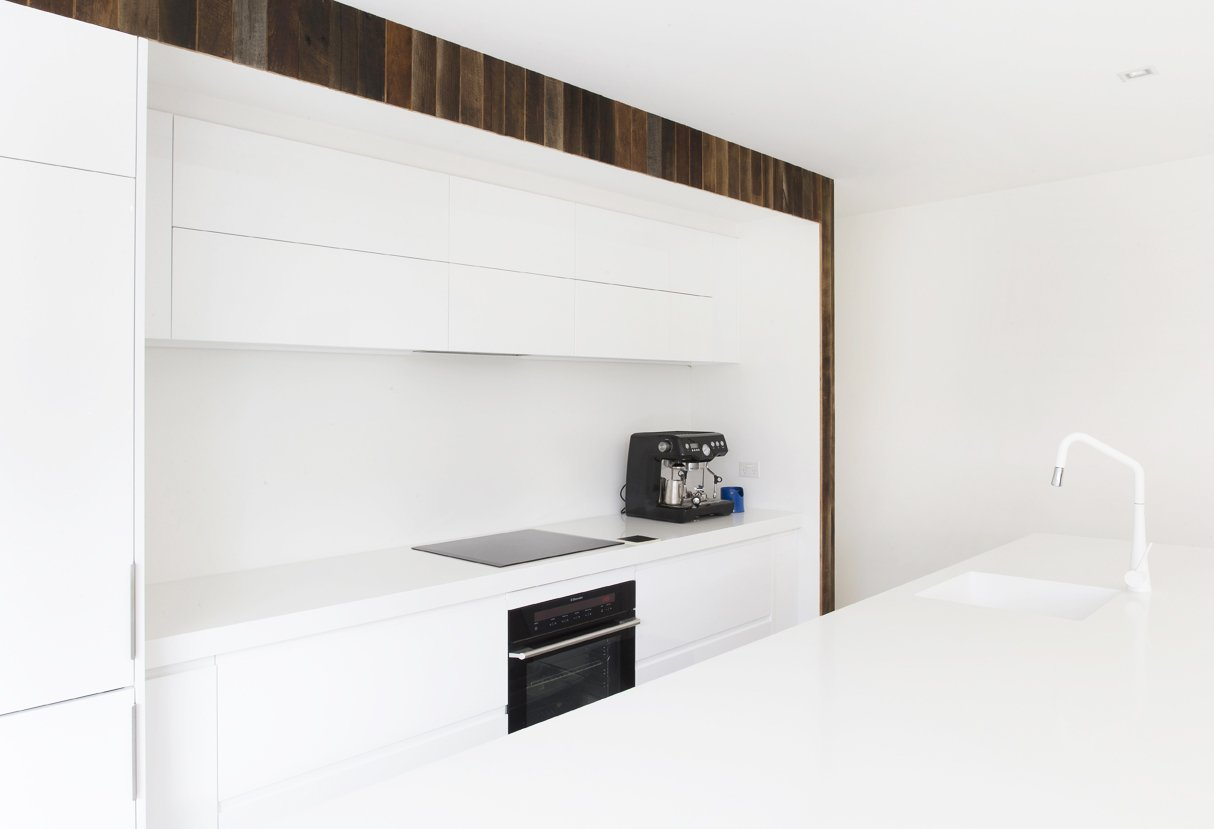 Black Electrolux induction cooktop and electric oven offer graphic contrast to the minimal white Corian counters and white cabinetry in the home's kitchen.  1850s Prefab Cottage from Boston Finds New Life in Australia by Sarah Akkoush