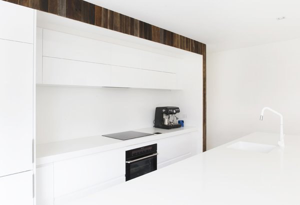 Black Electrolux induction cooktop and electric oven offer graphic contrast to the minimal white Corian counters and white cabinetry in the home's kitchen.