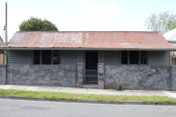 The original home is seen before the dramatic transformation. During the demolition, roof shingles were uncovered beneath the corrugated iron sheeting. It was theorized that the home could have originally been a general store, halfway house, or possibly even a brothel.