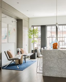 """[The owner] needed a good working kitchen, the ability to seat up to 20 at dining tables, and accommodate over 100 for cocktails and fundraisers,"" Walker said. The Tonon Wave chairs  are covered in Dalmatian upholstery by Calvin Fabrics; they sit on a Bursa Wool Rug from West Elm."