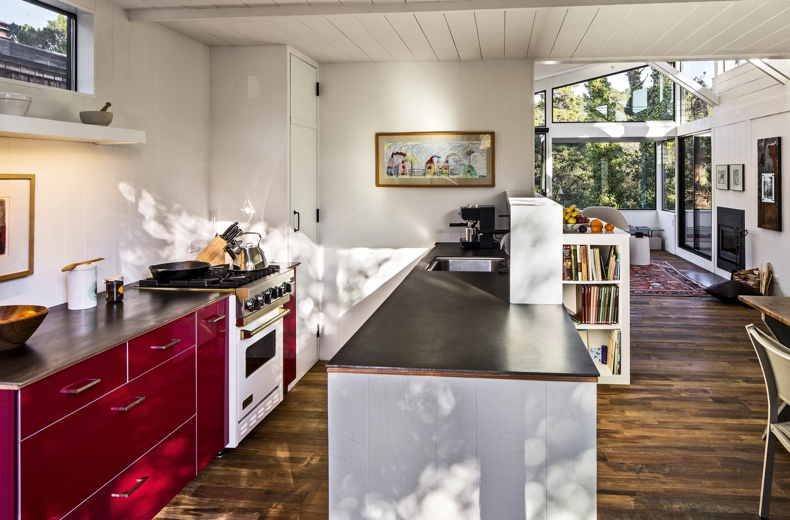 This house in Carmel by the Sea is enlivened by its very red kitchen cabinetry. By knocking down a dividing wall, the architects opened the kitchen up to the rest of the living space. Ikea red lacquer cabinetry and Caesarstone countertops replace dingy cupboards and old-fashioned finishes. Stainless steel appliances help ground the airy, open space.  Photo 7 of 10 in Bright Renovation of a 1970s Big Sur Home from Torres House